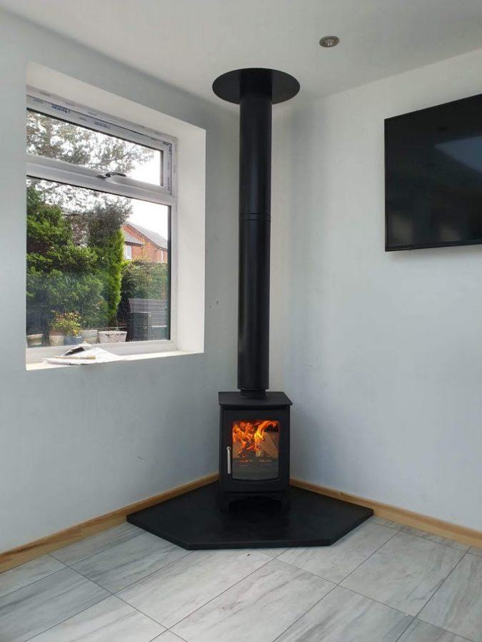 A lit corner stove resting on a custom-made pentagonal slate hearth