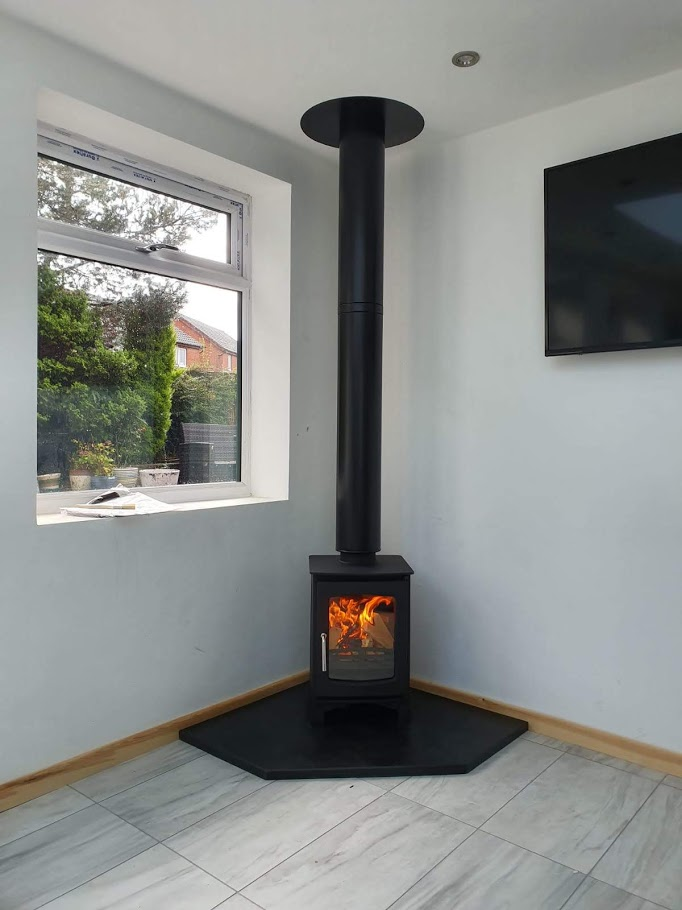 A lit corner stove resting on a custom-made pentagonal slate hearth