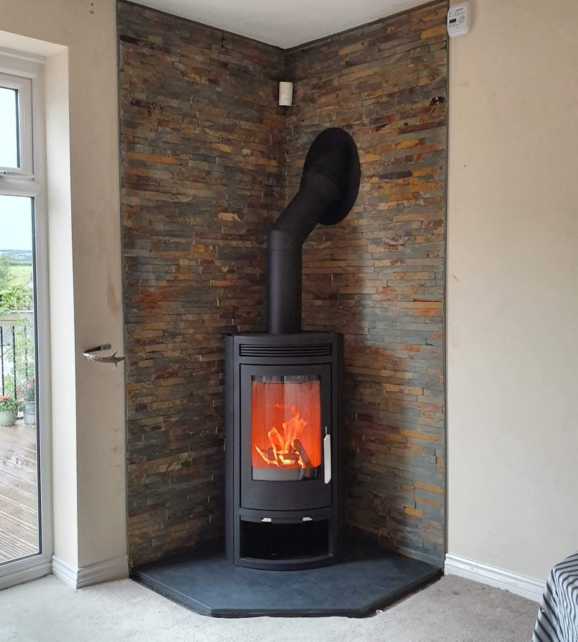 One of our bespoke five-sided pentagonal slate hearths with a corner stove