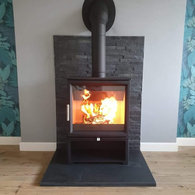 Contemporary square slate hearth now in use with its stove