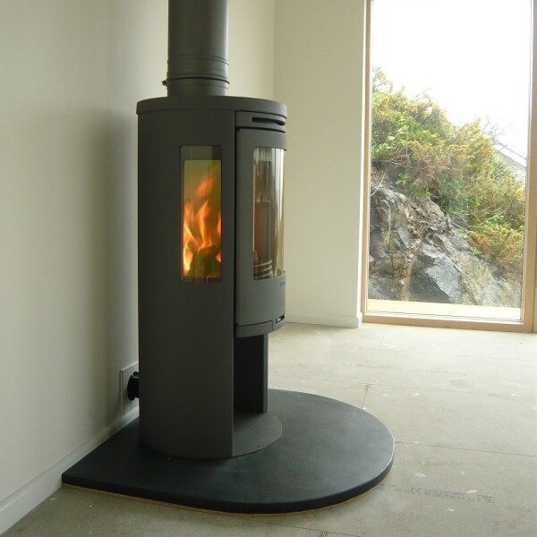 Curved front edge slate hearth with fire in a living room