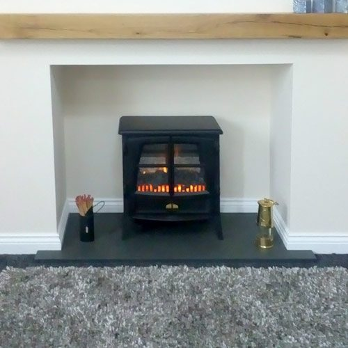 Made-to-measure T-shaped slate hearth with lit stove