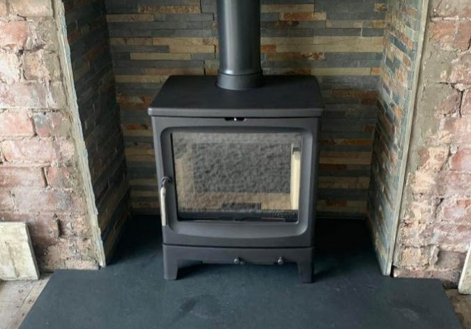 Traditional stove on one of our bespoke T-shape slate hearths